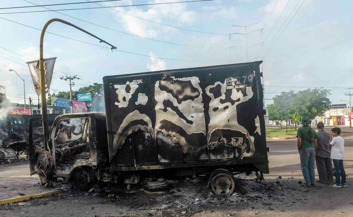 """A burnt out truck used by gunmen smolders on an intersection, a day after street battles between gunmen and security forces in Culiacan, Mexico, Friday Oct. 18, 2019. Mexican security forces backed off an attempt to capture a son of imprisoned drug lord Joaquin """"El Chapo"""" Guzman after finding themselves outgunned in a ferocious shootout with cartel enforcers that left at least eight people dead and more than 20 wounded, authorities said. (AP Photo/Augusto Zurita)"""