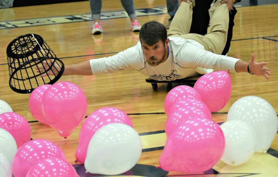 Needville High School football coach Tyler Lawson rolls onto the gym floor to gather balloons in a fast-moving game of teachers vs. students during the Friday, Oct. 11, Pink Out Pep Rally in support of Breast Cancer Awareness Month. Photo: Needville High School / Needville High School
