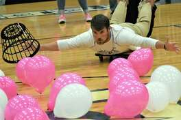 Needville High School football coach Tyler Lawson rolls onto the gym floor to gather balloons in a fast-moving game of teachers vs. students during the Friday, Oct. 11, Pink Out Pep Rally in support of Breast Cancer Awareness Month.