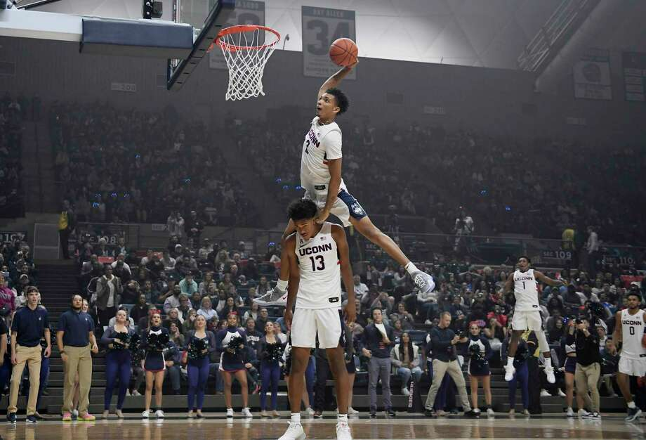 Connecticut's James Bouknight, top, leaps over teammate Richard Springs to dunk the ball during UConn's men's and women's basketball teams' annual First Night celebration in Storrs, Conn. (AP Photo/Jessica Hill) Photo: Jessica Hill / Associated Press / Copyright 2019 The Associated Press. All rights reserved