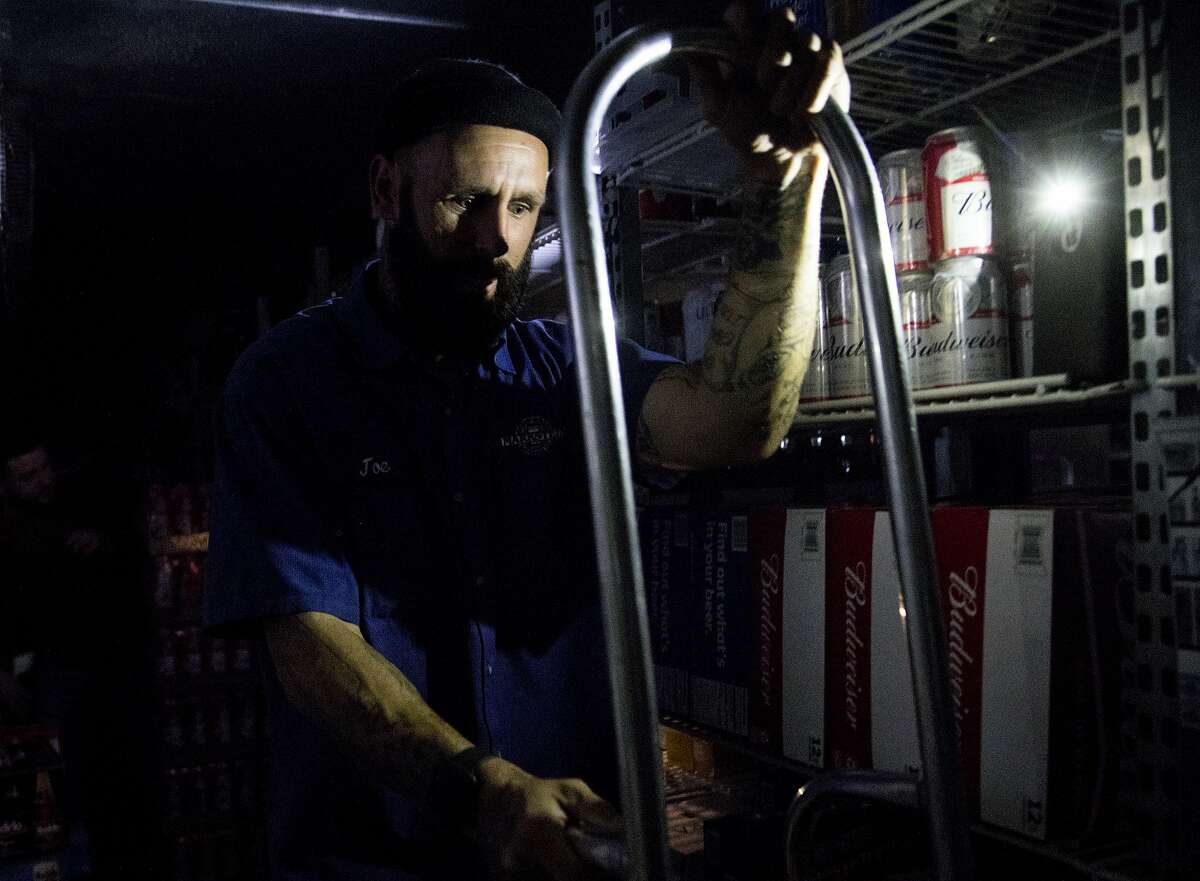 Beer distributor Joe Wheeler restocks beer by the flashlight of a cell phone at La Tapatia Market in Napa, Calif. Wednesday, Oct. 9, 2019 following the first stage of PG&E Public Safety Power Shutoffs across Northern California.