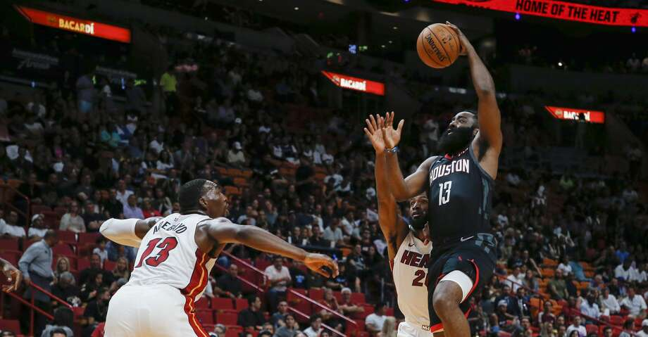 Houston Rockets guard James Harden (13) goes high to score against Miami Heat defenders Bam Adebayo (13) and Justise Winslow (20) during the first quarter of an NBA preseason basketball game Friday, Oct. 18, 2019, in Miami. (AP Photo/Joe Skipper) Photo: Joe Skipper/Associated Press