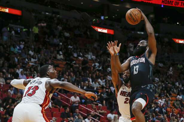 Houston Rockets guard James Harden (13) goes high to score against Miami Heat defenders Bam Adebayo (13) and Justise Winslow (20) during the first quarter of an NBA preseason basketball game Friday, Oct. 18, 2019, in Miami. (AP Photo/Joe Skipper)