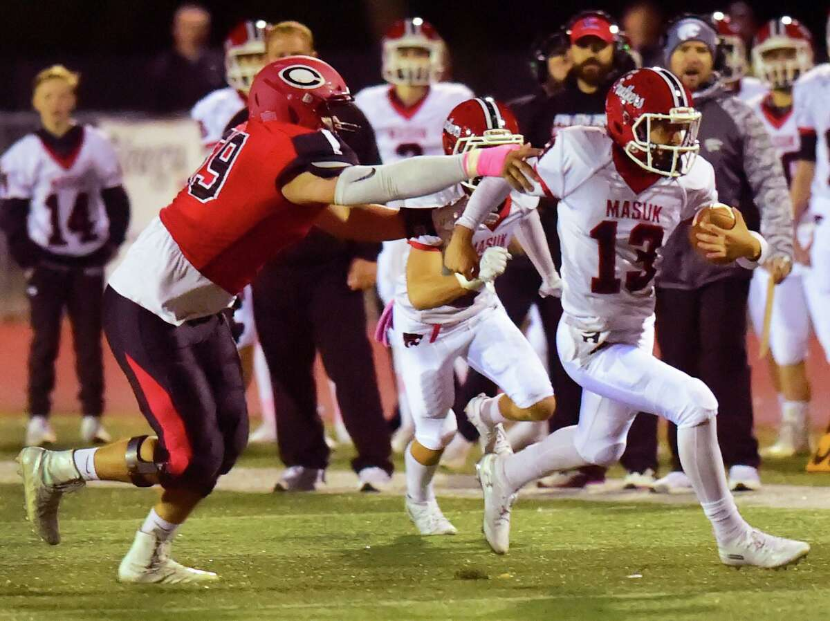 Cheshire, Connecticut - Friday, October 18, 2019: William Bergin of Cheshire H.S., left, tries to catch Nicholas Saccu of Masuk during first quarter football Friday at Cheshire H.S.