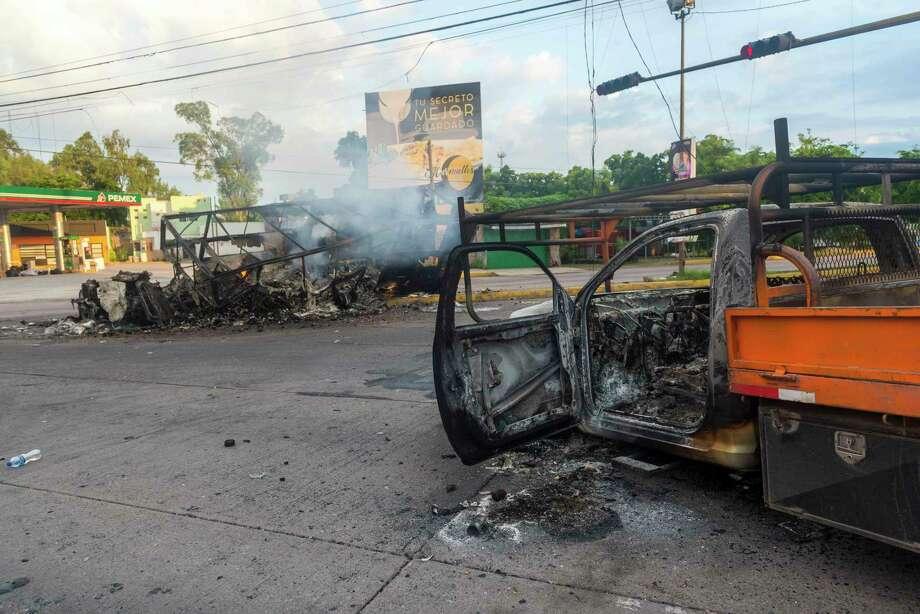 Vehículos quemados utilizados por hombres armados continúaban quemándose en la calle, un día después de los enfrentamientos entre pistoleros y las fuerzas del orden en Culiacán, México, el viernes 18 de octubre de 2019. Photo: Augusto Zurita /Associated Press / Copyright 2019 The Associated Press. All rights reserved.
