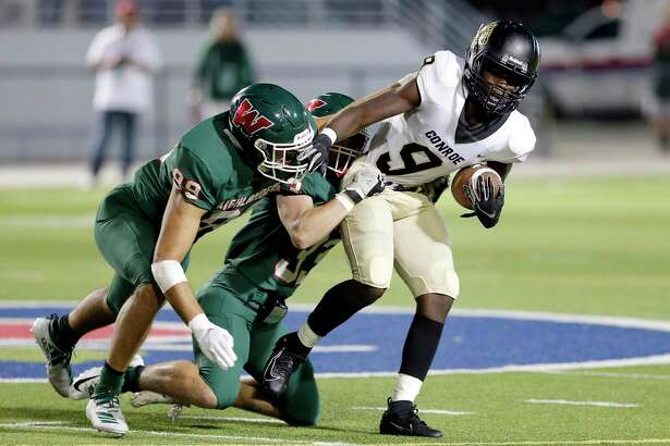 Conroe wide receiver Jalen Williams (9) is caught by The Woodlands' Simon Cruz (99) and Noah Polotko (33) during the first half of their game at Woodforest Bank Stadium Friday, Oct. 18, 2019 in Shenandoah, TX.