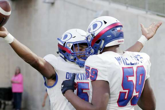 Dickinson quarterback Mike Welch (5) and offensive lineman P.J. Williams (59) celebrate Welch's touchdown during the first half of a high school football game against Taylor Friday, Sept. 20, 2019 in Katy, TX.