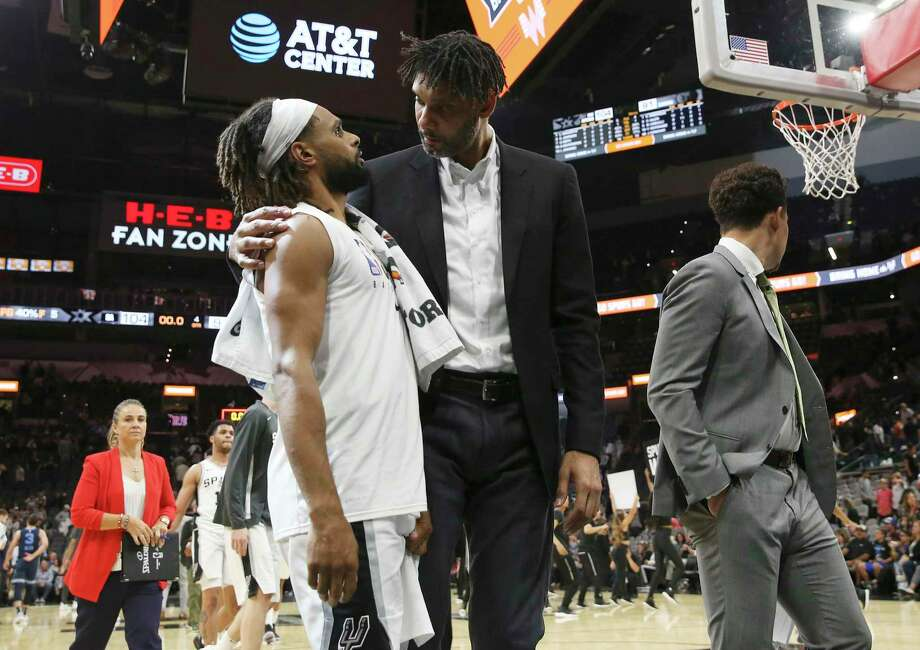 Spurs assistant coach Tim Duncan (center) walks off the court with Patty Mills after the pre-season game against the Memphis Grizzlies at the AT&T Center on Friday, Oct. 18, 2019. Spurs win 104-91 over the Grizzlies. Photo: Kin Man Hui, Staff / Staff Photographer / ©2019 San Antonio Express-News