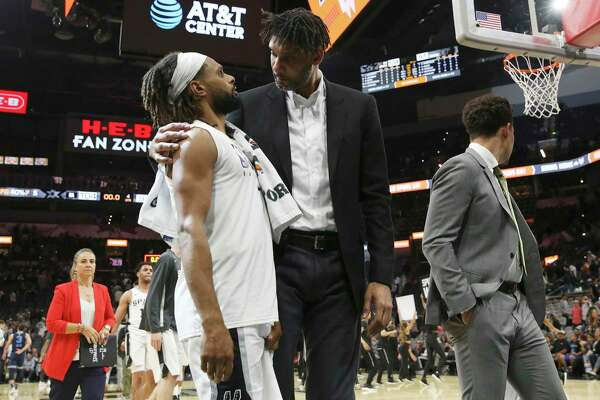 Spurs assistant coach Tim Duncan (center) walks off the court with Patty Mills after the pre-season game against the Memphis Grizzlies at the AT&T Center on Friday, Oct. 18, 2019. Spurs win 104-91 over the Grizzlies. (Kin Man Hui/San Antonio Express-News)