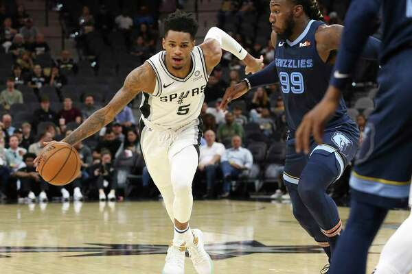Spurs' Dejounte Murray (05) drives toward the basket against Memphis Grizzlies' Jae Crowder (99) in pre-season action at the AT&T Center on Friday, Oct. 18, 2019. (Kin Man Hui/San Antonio Express-News)