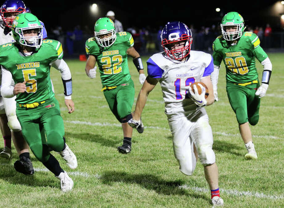 Carlinville's Joe Leiws (12) breaks away for a 38-yard run with Southwestern's Gavin Day (5), Jacob Fisher (22) and Pauly Garrett (20) in pursuit early in the third quarter Friday night at Knapp Field in Piasa. Photo: Greg Shashack / The Telegraph