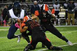 Edwardsville's Eric Epenesa, left, and Jacob Morrissey team up for a tackle in the first quarter.
