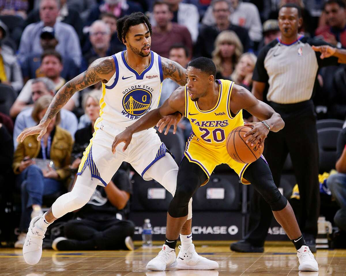 Los Angeles Lakers guard Demetrius Jackson (20) is defended by Golden State Warriors guard D'Angelo Russell (0) during the first half of an NBA preseason game at Chase Center on Friday, Oct. 18, 2019, in San Francisco, Calif.