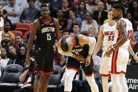 Houston Rockets guard Russell Westbrook (0) heads off the court after hurting his right hand, as Miami Heat forward Chris Silva (30) stands nearby during the fourth quarter of an NBA preseason basketball game Friday, Oct. 18, 2019, in Miami. The Rockets won 144-133. (AP Photo/Joe Skipper)