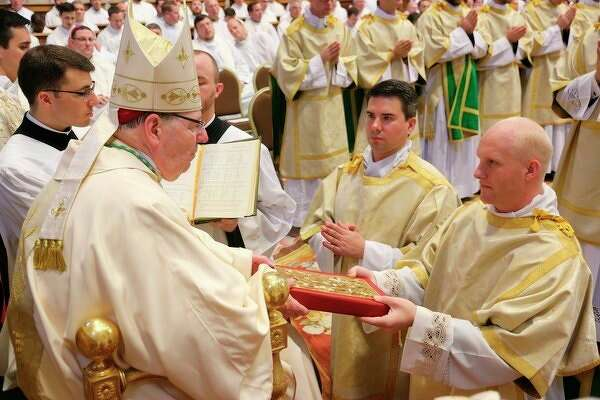 Vested as a deacon, Alex Kowalkowski kneels before the bishop and ispresented with the Books of the Gospel.(Courtesy photo/PNAC Photo Service)