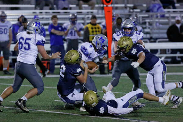 Quincy Notre Dame's Zac Becker (2) takes down Marquette's Logan Sternickle Friday night at QND's Advance Physical Therapy Field. |