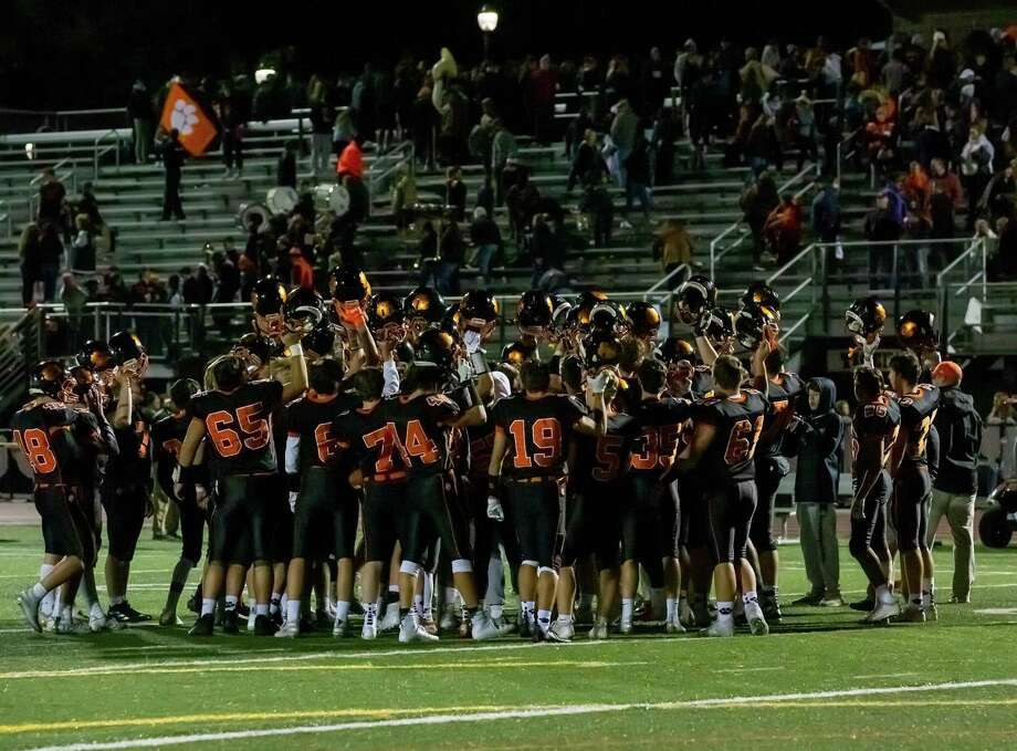 The Ridgefield football team celebrates at the end of Friday night's homecoming win over arch-rival Wilton. Photo: Gretchen McMahon / For Hearst Connecticut Media