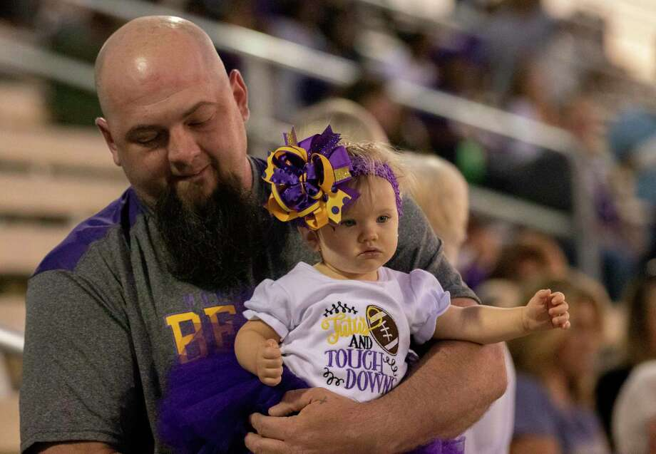 Aaron Langley carries his daughter Coralee May Langley as she is dressed in the Montgomery High School colors and a football T-shirt before a District 10-5A (Div. II) football game at MISD Stadium in Montgomery. Photo: Cody Bahn, Houston Chronicle / Staff Photographer / © 2019 Houston Chronicle