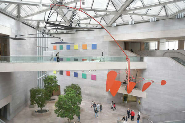An untitled Alexander Calder aluminum-and-steel mobile hangs from the ceiling above visitors at the National Gallery of Art East Building on the National Mall in Washington, D.C.