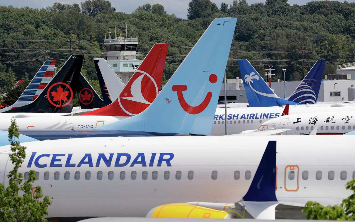 FILE - In this June 27, 2019, file photo dozens of grounded Boeing 737 MAX airplanes crowd a parking area adjacent to Boeing Field in Seattle. Passengers who refuse to fly on a Boeing Max wona€™t be entitled to compensation if they cancel. However, travel experts think airlines will be very flexible in rebooking passengers of giving them refunds if theya€™re afraid to fly on a plane that has crashed twice. (AP Photo/Elaine Thompson, File)