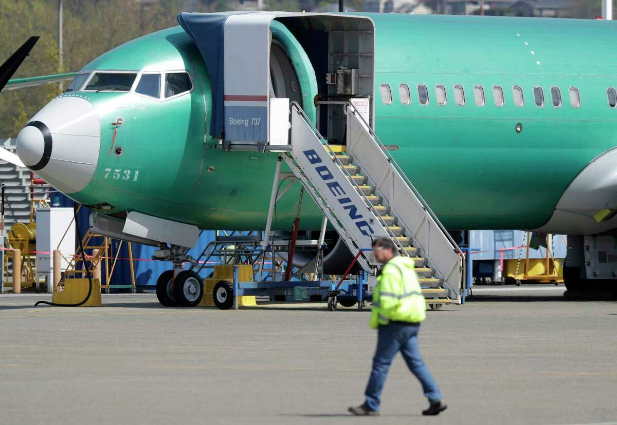 FILE - In this April 26, 2019, file photo a worker walks past a Boeing 737 MAX 8 airplane being built for Oman Air at Boeing's assembly facility in Renton, Wash. Passengers who refuse to fly on a Boeing Max wona€™t be entitled to compensation if they cancel. However, travel experts think airlines will be very flexible in rebooking passengers of giving them refunds if theya€™re afraid to fly on a plane that has crashed twice. (AP Photo/Ted S. Warren, File)