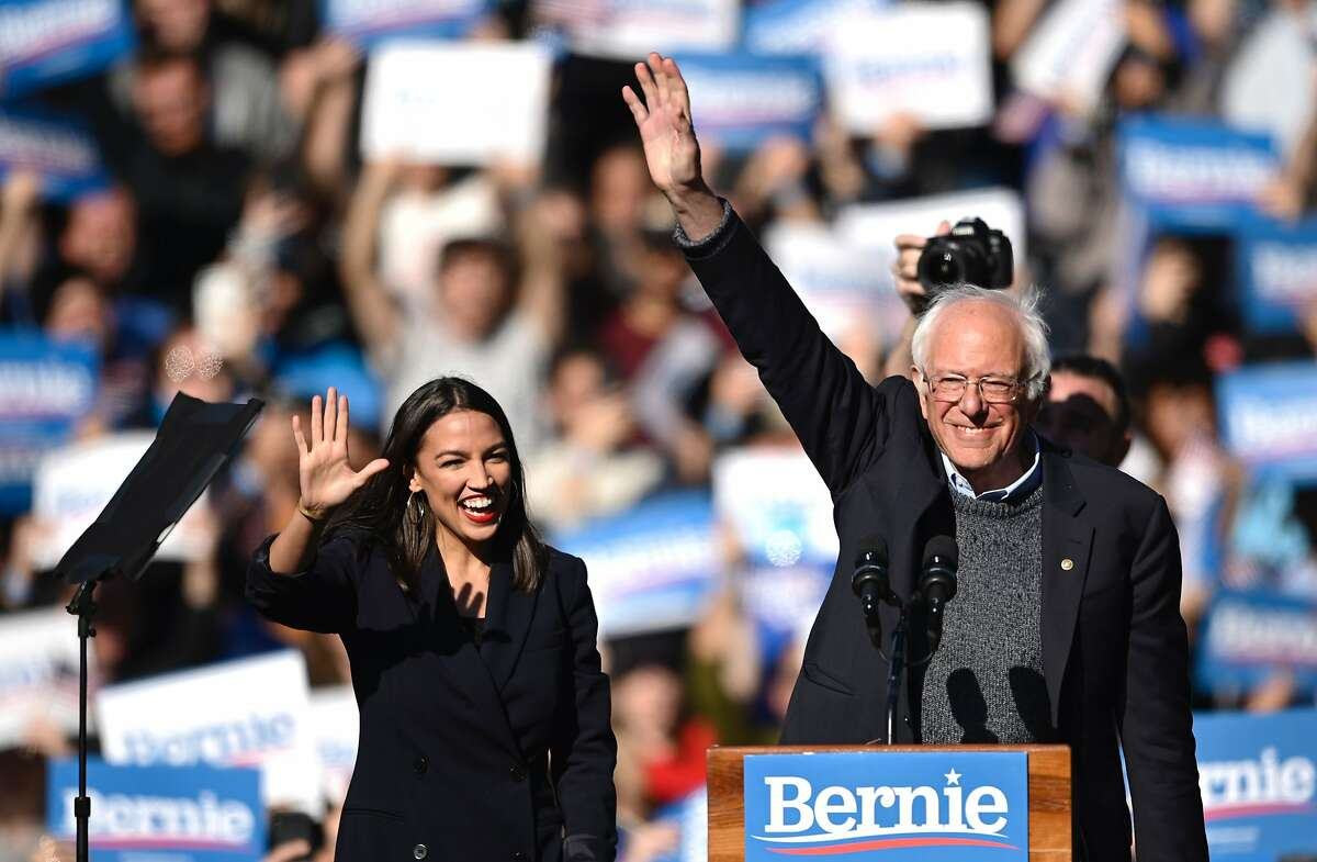 2020 Democratic presidential hopeful US Senator Bernie Sanders (D-VT) and representative Alexandria Ocasio-Cortez (D-NY) wave to a crowd of supporters during a campaign rally on October 19, 2019 in New York City. (Photo by Johannes EISELE / AFP) (Photo by JOHANNES EISELE/AFP via Getty Images)