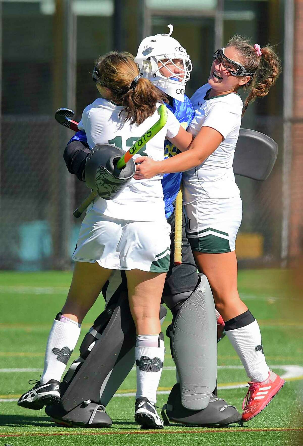 Sacred Heart goalie Olivia Caponiti celebrates the Tigers 3-0 win over Greenwich Academy with teammates Morgan Smith (15) and Marygrace Farrell (13) following an FAA girls field hockey match on Oct. 19, 2019 in Greenwich, Connecticut.
