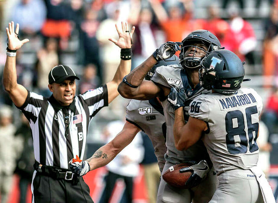 Josh Imatorbhebhe of Illinois, second from right, celebrates with teammates including Donny Navarro (86) after scoring a touchdown in the second half of Saturday's game against wisconsin in Champaign. Illinois won 24-21. Photo: Holly Hart | AP Photo