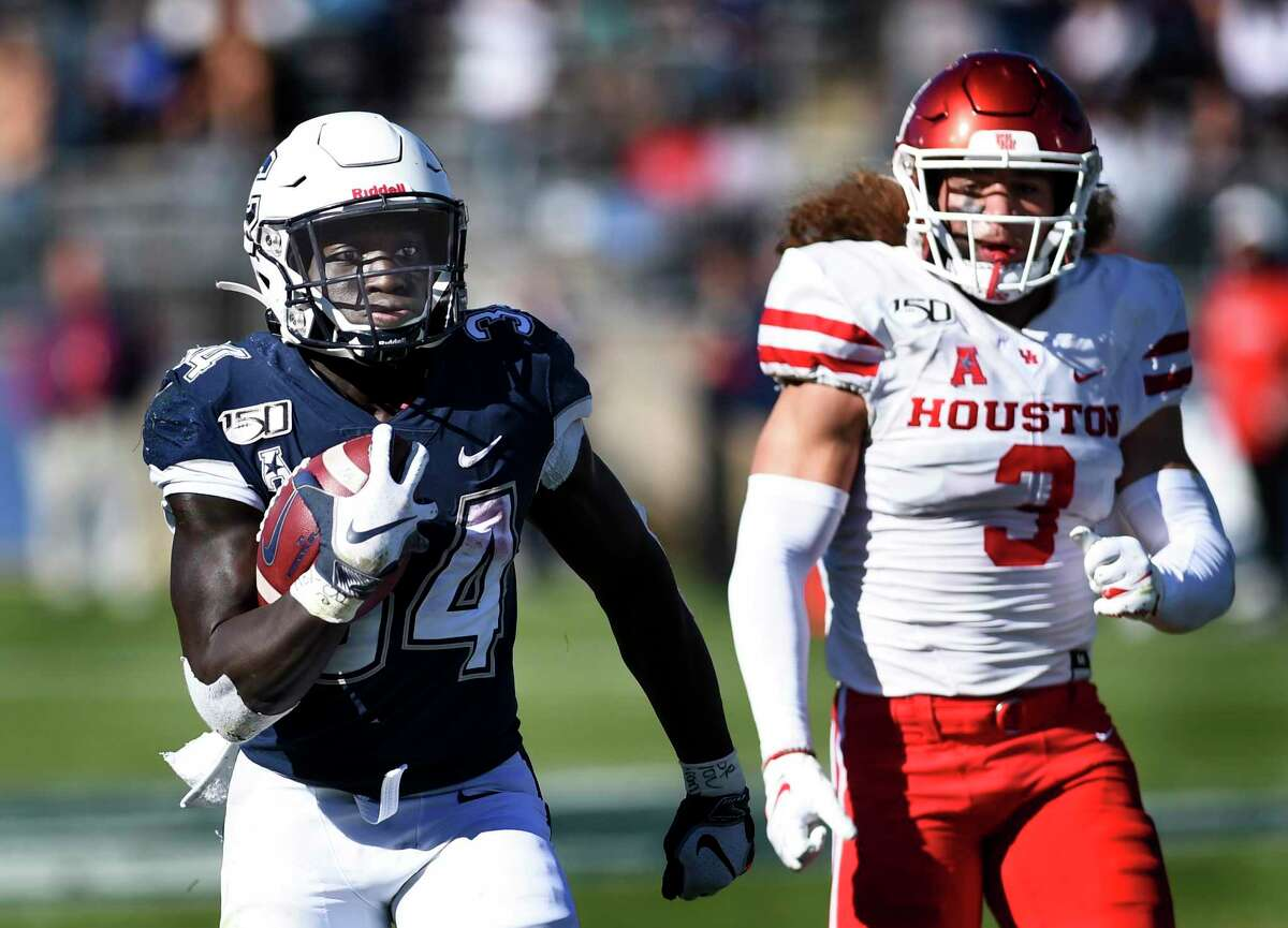 UConn running back Kevin Mensah (34) gains yardage against Houston linebacker Jordan Carmouche (8) during the second half of an NCAA college football game on Saturday, Oct. 19, 2019, in East Hartford, Conn.