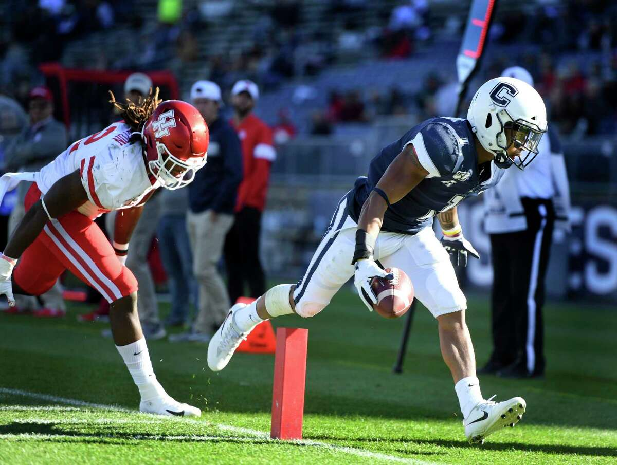 UConn running back Art Thompkins (1) scores while being chased by Houston linebacker Terrance Edgeston (42) during the second half of an NCAA college football game on Saturday in East Hartford, Conn.