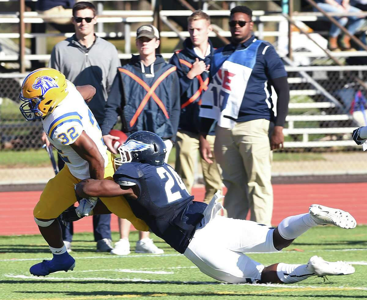 Shamar Logan (left) of UNH is tackled by Mekhi Barnett of SCSU near the goal line in the first half on October 19, 2019.