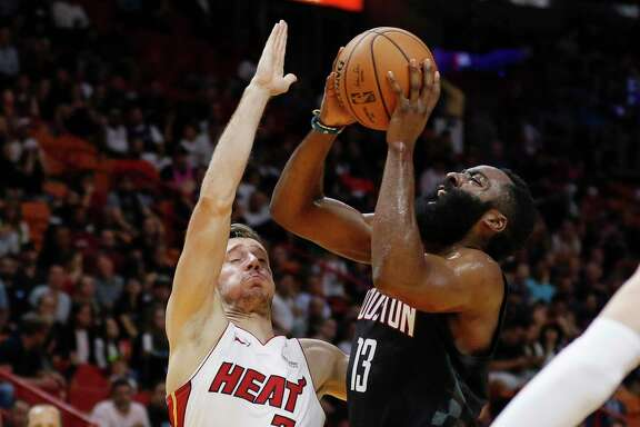 Houston Rockets guard James Harden (13) shoots next to Miami Heat guard Goran Dragic (7) during the first quarter of an NBA preseason basketball game Friday, Oct. 18, 2019, in Miami. (AP Photo/Joe Skipper)