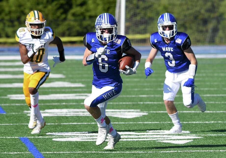 Darien's Michael Minicus (6) breaks free for a touchdown with Trinity Catholic/Wright Tech's Luigi Bernard (10) in pursuit during a football game at Darien High School on Saturday, Oct. 19, 2019. Photo: Dave Stewart / Hearst Connecticut Media / Hearst Connecticut Media