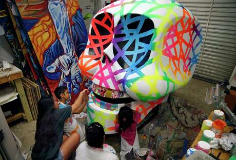 Alexis Hishikawa,L, volunteer student from UTSA, L, helps Boney Perez,7, to put the finishing touches on San Anto Program Day of The Dead skull on Thursday October 17, 2019. The 4'x2.5' skull will be displayed on Houston Street as part of a street art exhibition. On the right Yajaira Perez watches her daughter Allison Perez,4, work on the sculpture.