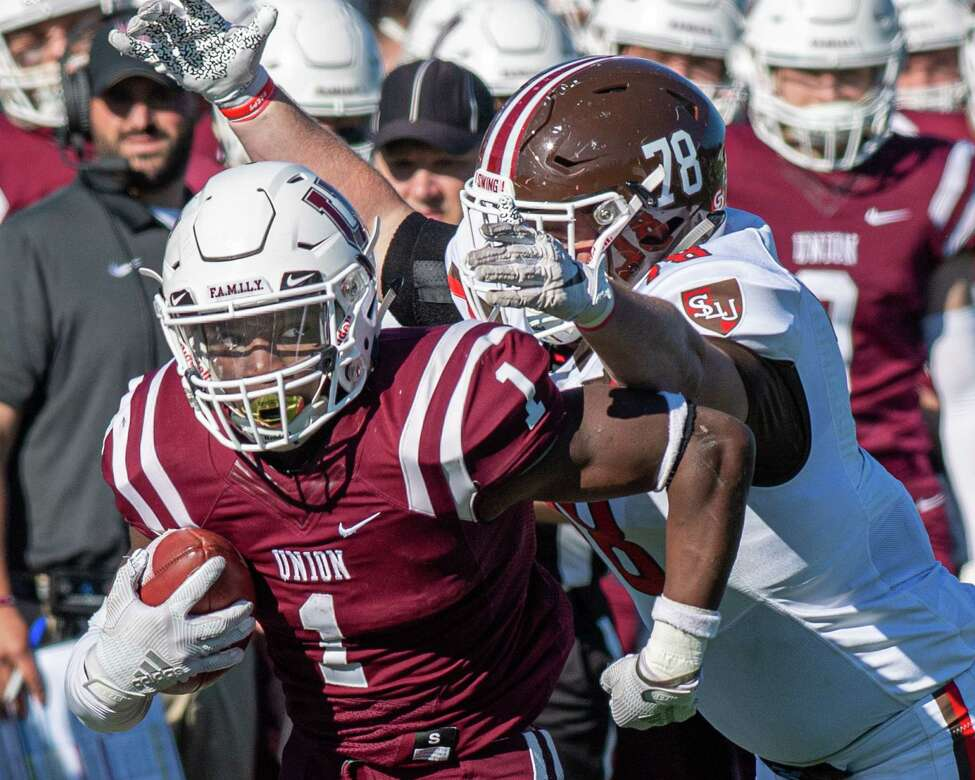 Union College running back Ike Irabor looks over his shoulder at a looming St. Lawrence defensive lineman Reece Gillette during a game at Union College on Saturday, Oct. 19, 2019 (Jim Franco/Special to the Times Union.)