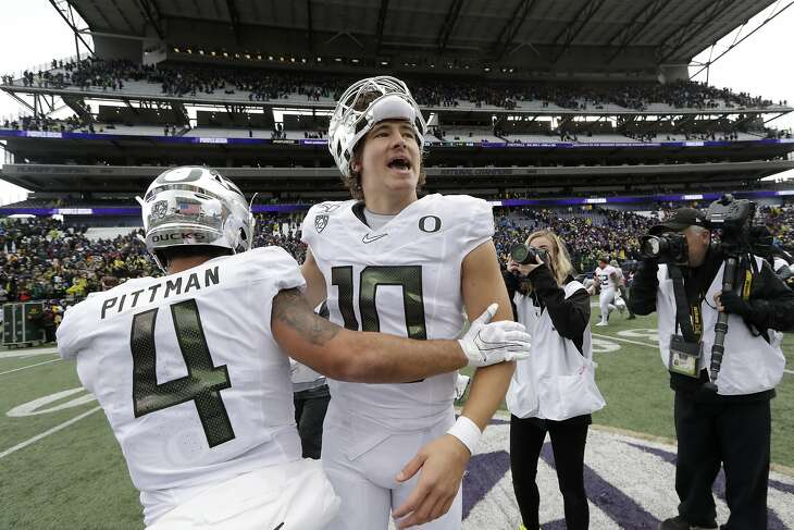 Oregon quarterback Justin Herbert (10) is embraced by Mycah Pittman after the team beat Washington in an NCAA college football game Saturday, Oct. 19, 2019, in Seattle. Oregon won 35-31. (AP Photo/Elaine Thompson)