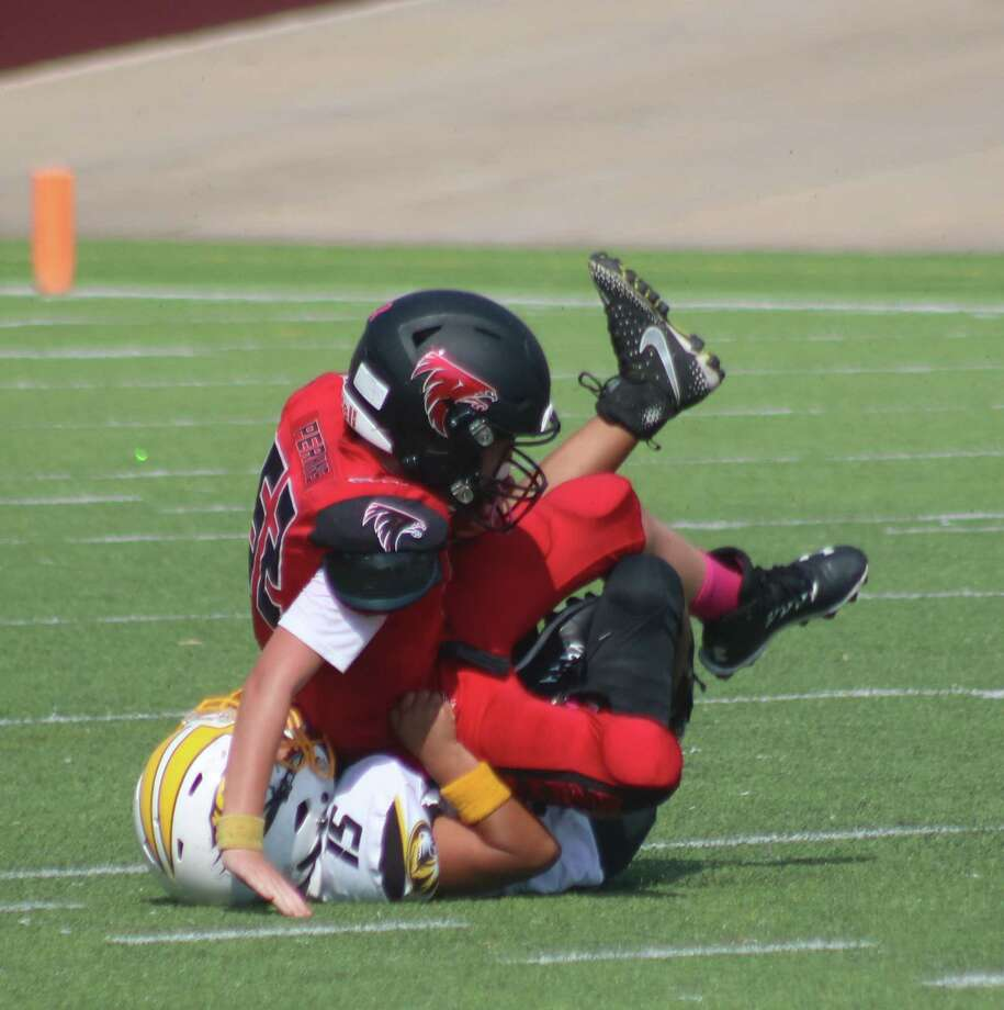 Deer Park Junior Tiger player Ayden Luna sacks Clear Lake Falcon quarterback Logan Perkins during the final seconds of Saturday's game, helping to preserve the Tigers' 14-7 win. Photo: Robert Avery