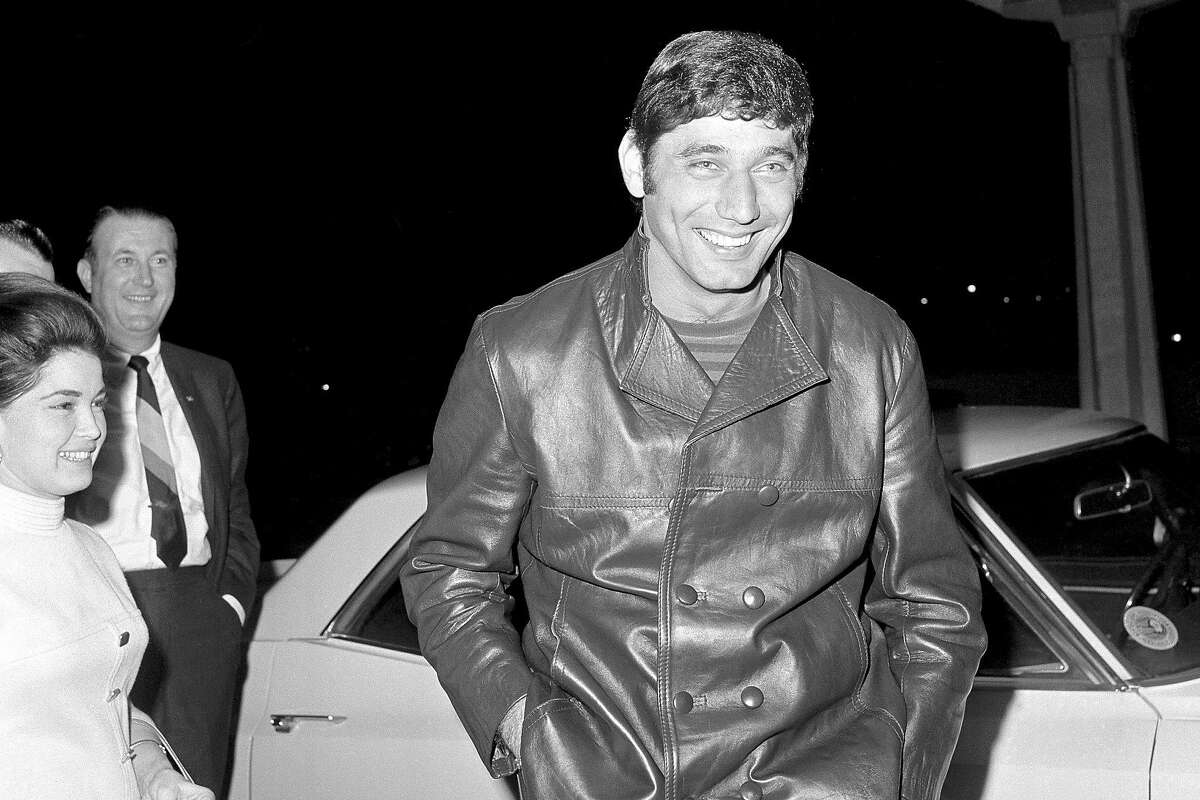 FILE - In this Jan. 19, 1969, file photo, New York Jets quarterback Joe Namath smiles as he arrives at the stadium in Jacksonville, Fla. Namath is the NFL's greatest character. Guaranteed. The Pro Football Hall of Fame quarterback who guaranteed his three-touchdown underdog New York Jets would beat the mighty Baltimore Colts in the third Super Bowl was a solid choice in balloting conducted by The Associated Press in conjunction with the league's celebration of its 100th season. (AP Photo/File)