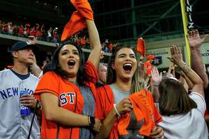 Krystianna Guerra and Larissa Oswald celebrate the three-run home run Houston Astros first baseman Yuli Gurriel (10) hit during the first inning of Game 6 of the American League Championship Series at Minute Maid Park in Houston on Saturday, Oct. 19, 2019.
