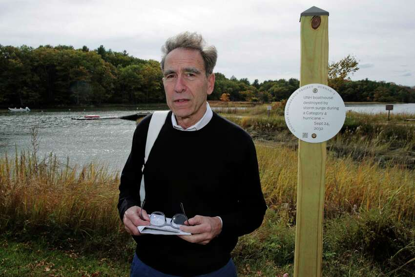 Artist Thomas Starr poses next to a sign, part of a public design installation, on the banks of the Oyster River in Durham, N.H., Wednesday, Oct. 16, 2019. Starr, a graphic and information design professor from Boston's Northeastern University, created the project to address possible effects of climate change. (AP Photo/Charles Krupa)