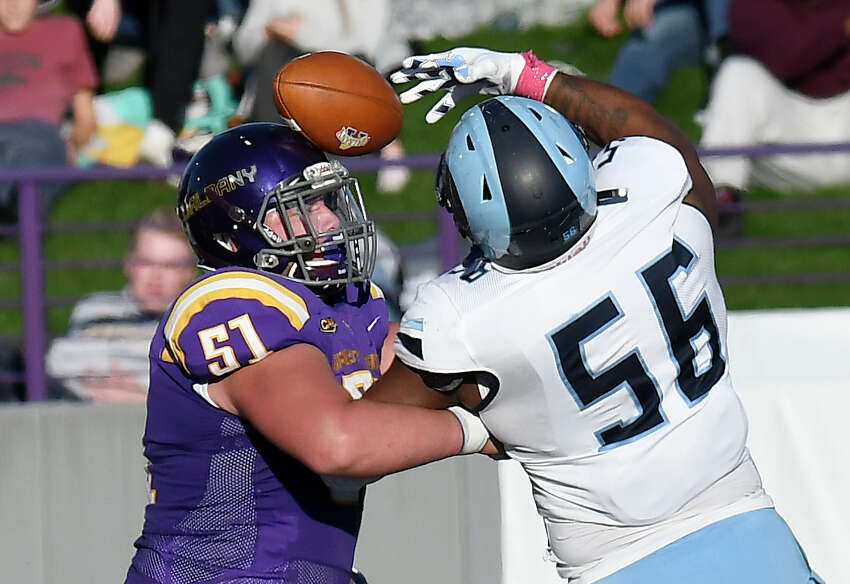 University at Albany offensive lineman Niko Culnan (51) and Rhode Island defensive lineman Keith Wells (56) chase a tipped ball during the first half of an NCAA football game Saturday, Oct. 19, 2019, in Albany, N.Y.
