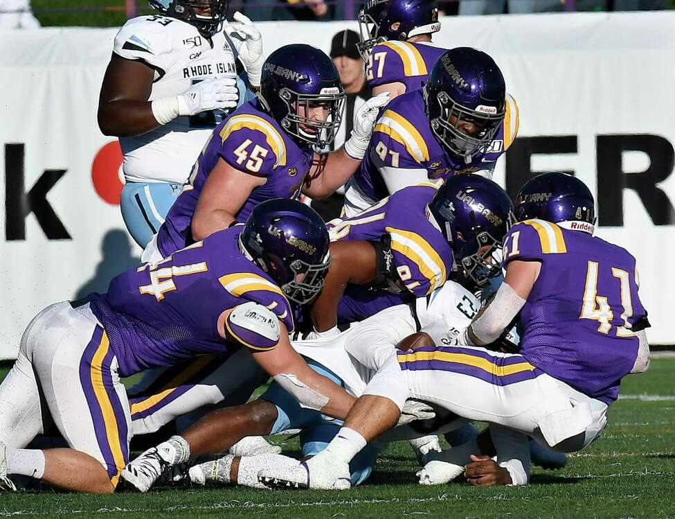 University at Albany players tackle Rhode Island running back Naim Jones (23) during the first half of an NCAA football game Saturday, Oct. 19, 2019, in Albany, N.Y.