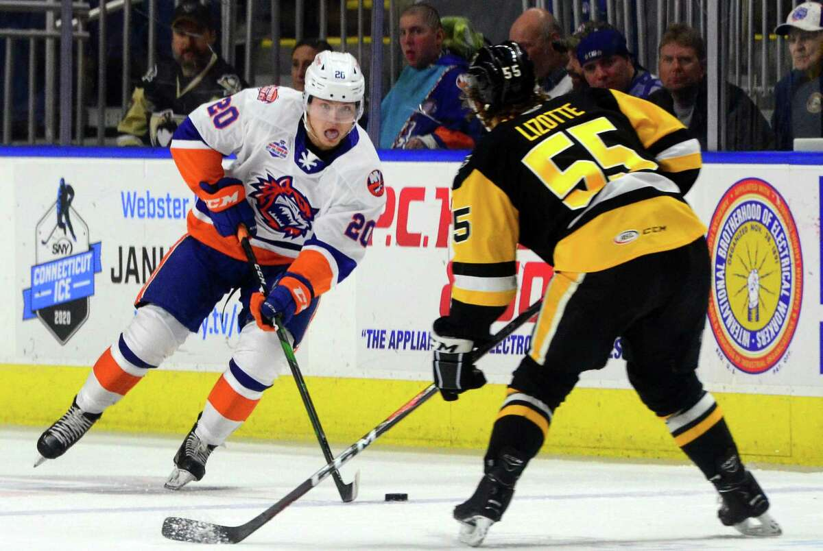 Sound Tigers' Kieffer Bellows (20), left, drives the puck as W-B/Scranton Penguins' Jon Lizotte (55) defends during AHL hockey action at the Webster Bank Arena in Bridgeport, Conn., on Satuday Oct. 19, 2019.