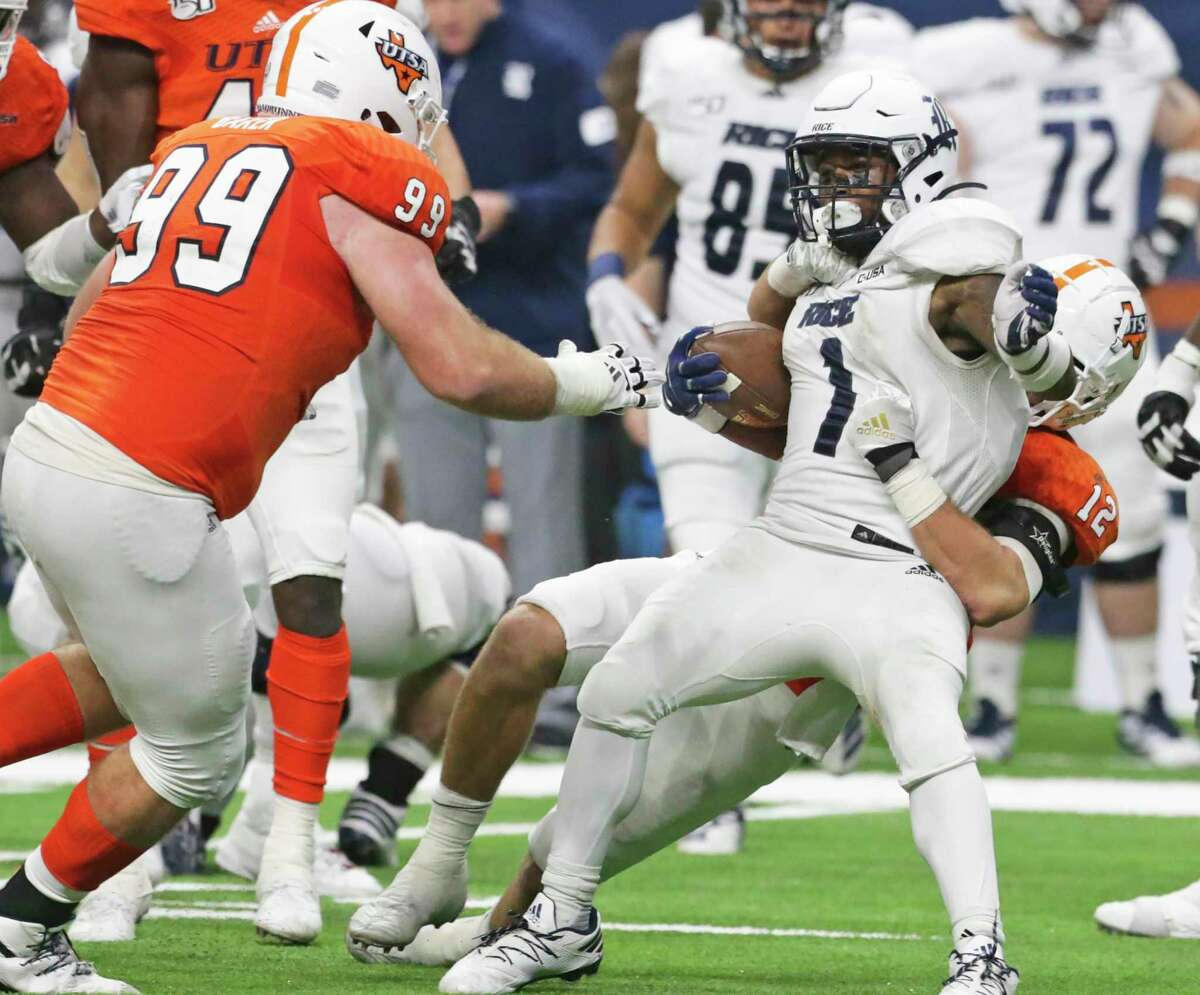 Owl running back Aston Walter is brought down by Roadrunner linebacker Andrew Martel as UTSA hosts Rice at the Alamodome on Oct. 19, 2019.