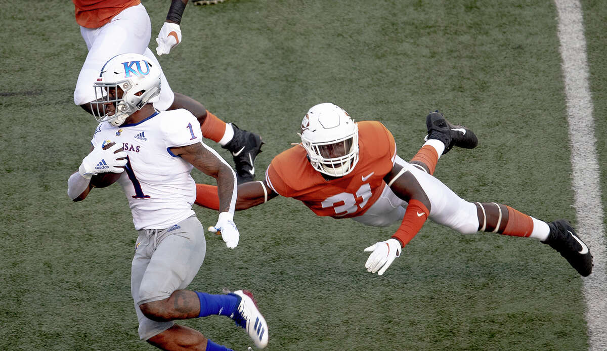 Texas defensive back DeMarvion Overshown (31) leaps to tackle Kansas running back Pooka Williams Jr. (1) during an NCAA college football game Saturday, Oct. 19, 2019, in Austin, Texas. (Nick Wagner/Austin American-Statesman via AP)