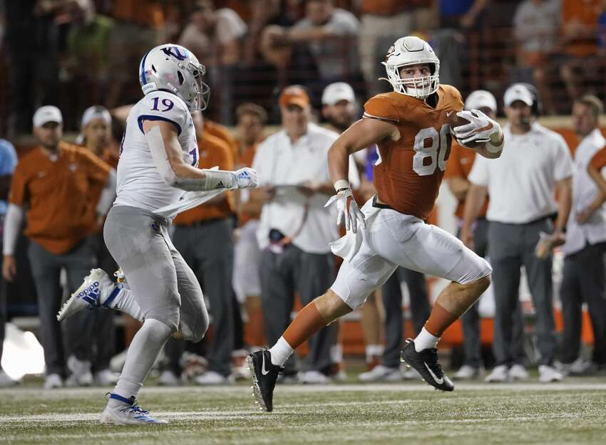 Texas' Cade Brewer (80) runs after a catch as Kansas' Gavin Potter (19) chases him during the second half of an NCAA college football game in Austin, Texas, Saturday, Oct. 19, 2019. (AP Photo/Chuck Burton)
