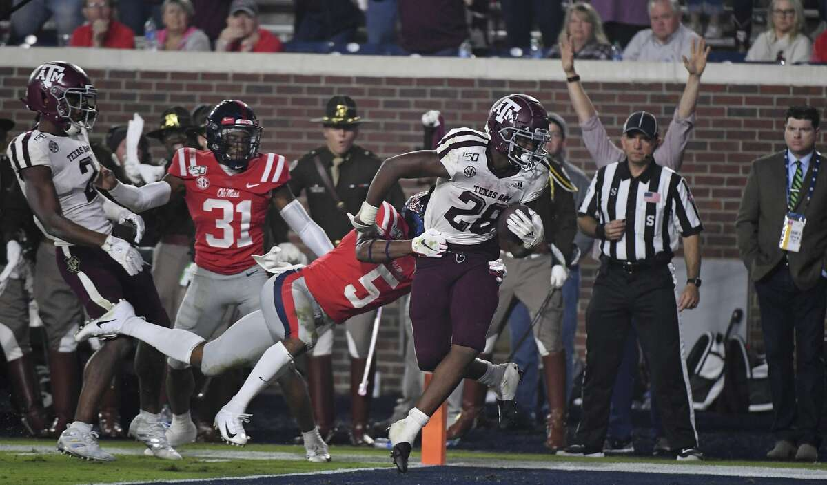 Texas A&M running back Isaiah Spiller (28) carries the ball past Mississippi defensive back Jon Haynes (5) for a 22-yard touchdown during the second half of an NCAA college football game in Oxford, Miss., Saturday, Oct. 19, 2019. Texas A&M won 24-17. (AP Photo/Thomas Graning)
