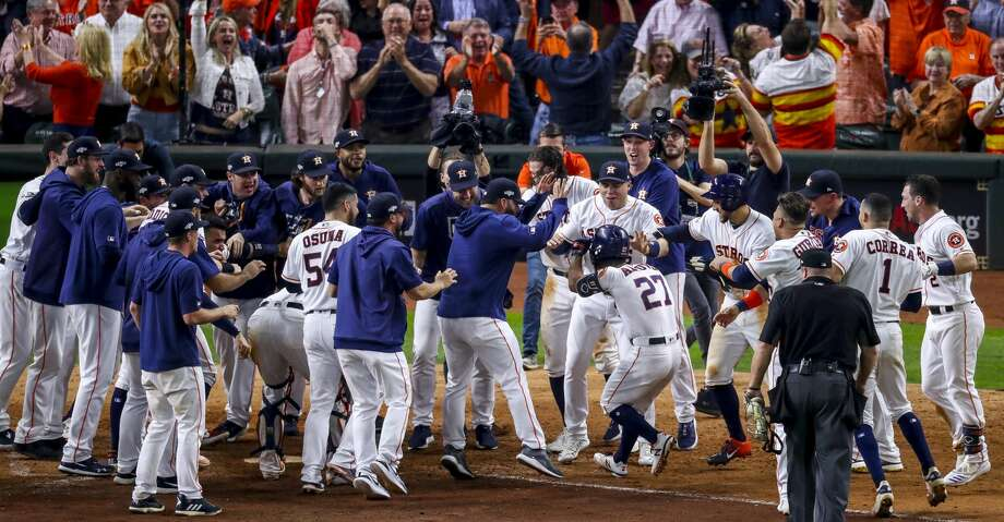 Houston Astros second baseman Jose Altuve (27) is celebrated at home plate after hitting a game-winning, two-run, walk-off home run to win Game 6 of the American League Championship Series in the ninth inning at Minute Maid Park in Houston on Saturday, Oct. 19, 2019. Photo: Godofredo A Vásquez/Staff Photographer