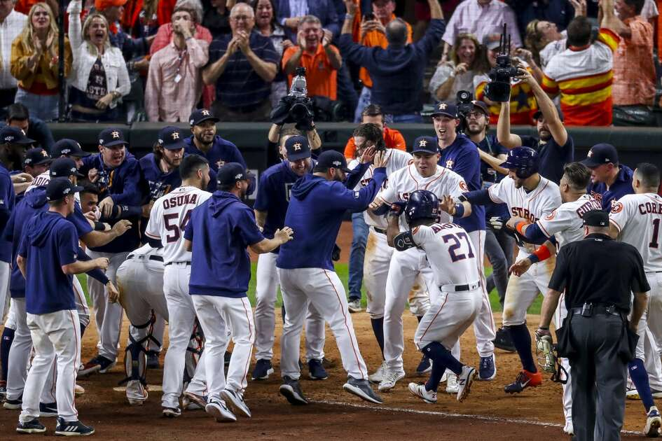 Houston Astros second baseman Jose Altuve (27) is celebrated at home plate after hitting a game-winning, two-run, walk-off home run to win Game 6 of the American League Championship Series in the ninth inning at Minute Maid Park in Houston on Saturday, Oct. 19, 2019.