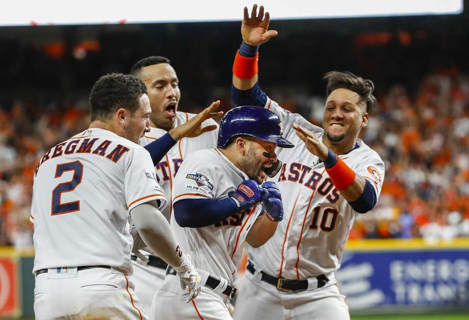 Houston Astros second baseman Jose Altuve (27) is celebrated at home plate after hitting a game-winning, two-run, walk-off home run to win Game 6 of the American League Championship Series in the ninth inning at Minute Maid Park in Houston on Saturday, Oct. 19, 2019. Photo: Brett Coomer/Staff Photographer